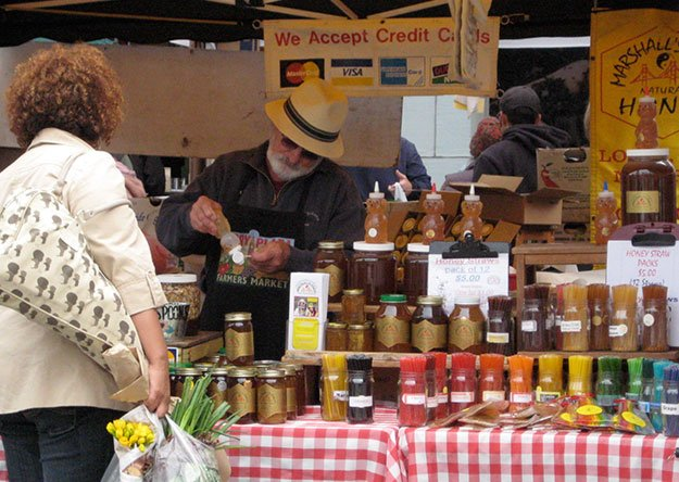 man is selling different types of honey in glass jars