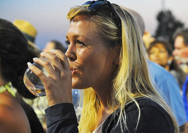 woman drinking glass of water outside