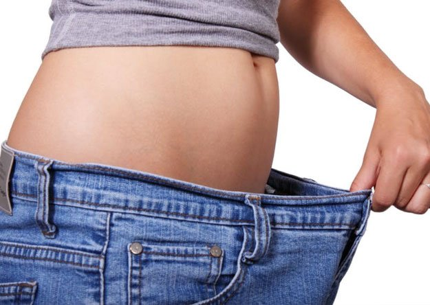woman is holding pants to show belly in diet