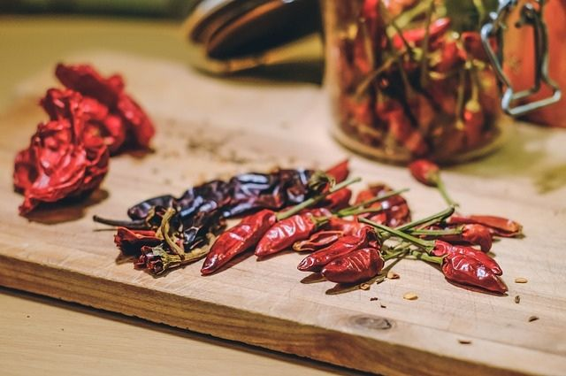 A handful of dried red chilis standing on a kitchen table for food preparing.