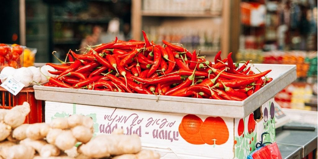 100 pieces of Red Chilis are presented on a food market in a box.